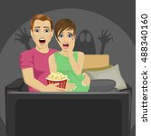 young couple watching horror... | Shutterstock .eps vector #488340160