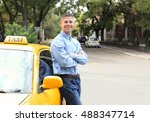 Small photo of Male taxi driver near car