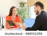 Small photo of Saleswoman trying to sell products to a client showing them in a tablet at office