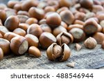 Small photo of Hazelnut kernels and whole hazelnuts on old brown table, selective focus