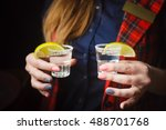 girl holds two shots of tequila   Shutterstock . vector #488701768