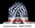 Small photo of A man covering his eye with his hand with imprint of an American flag for the concept: Justice is blind in United States of America.