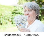 old age woman holding us dollars | Shutterstock . vector #488807023