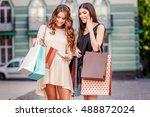 happy young women with shopping ... | Shutterstock . vector #488872024