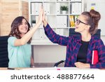 Small photo of Two colleagues are giving high five and celebrating a good deal they have just sealed. Concept of success.