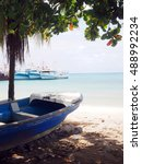 Small photo of panga fishing boat on shore Brig Bay Big Corn Island Nicaragua Central America with commerical fishing fleet in background in harbor