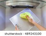 woman cleaning cooker hood with ...