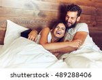 young couple lying in bed and... | Shutterstock . vector #489288406