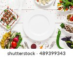 white ceramic plate surrounded... | Shutterstock . vector #489399343