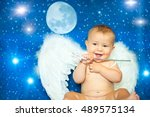 Small photo of Baby a few months with magic wand and angel wings plays on us blue sky and stars