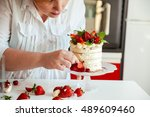 woman carefully icing the cake...   Shutterstock . vector #489609460