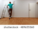 man on ladder while painting... | Shutterstock . vector #489655360