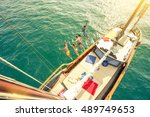 Small photo of Aerial view of young people jumping from sailing boat on sea trip - Rich happy friends having fun in summer party day - Exclusive vacation concept - Warm vintage filter with enhanced sun flare halos