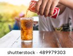 Small photo of BANGKOK,THAILAND SEPTEMBER 27 2016,Cola in a glass with glass on wooden table. On the background of men hands pouring cola in beaker. September 27 2016 Close up. Free space for text. Selective focus