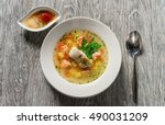 Beautiful presentation of the fish soup in a white plate, with double the sauce on a wooden background, top view.