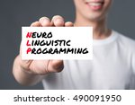 Small photo of NEURO LINGUISTIC PROGRAMMING (or NLP), message on the card shown by a man
