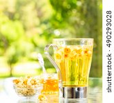 Small photo of Concept of herbal tea with honey and accessories. Camomile tea in a glass mug. Green meadow background. Light airy capture. Square