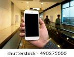 human hand holding white phone...