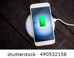 Small photo of White smartphone charging on a charging pad. Wireless charging