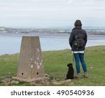 Stock photo female dog walker standing next to the trig point with on top of brean down a limestone promontory 490540936