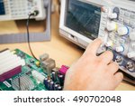 Small photo of Engineer tests electronic components with oscilloscope in the service center