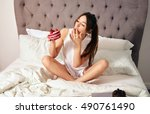 young woman in bed eating a... | Shutterstock . vector #490761490