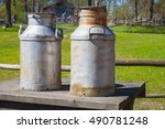 Two Metal Milk Churns Stand On...