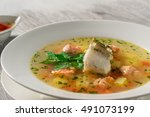 Beautiful presentation of the fish soup in a white plate, with double the sauce on a wooden background, close up.