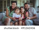 parents sitting on sofa with... | Shutterstock . vector #491262436