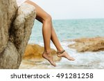 Close up of a legs of sexy woman in white skirt sit on edge of a rock. Concept of a danger, extreme. Beauty cute girl on a tropical beach sea ocean shore with large stones. Outdoor summer lifestyle.
