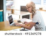 woman using a laptop and mobile ... | Shutterstock . vector #491369278