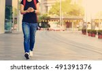 young woman walking with smart... | Shutterstock . vector #491391376