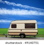 Vintage caravan on a parking lot with blue sky - stock photo