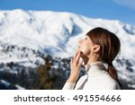 Small photo of portrait of a beautiful woman in snow with application of the protective cream in winter