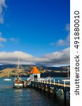 Small photo of AKAROA, NEW ZEALAND - MARCH: The orange roof hut of famous pier with blue sky on March, 2015, Akaroa, New Zealand