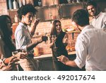 Small photo of Young and unstoppable. Cheerful young people dancing and drinking while enjoying home party on the kitchen