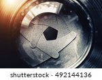Small photo of The diaphragm of old camera lens aperture with warm light bokeh. Selective focus with shallow depth of field. Vintage color tone filtered. Abstract texture background.