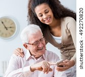 Small photo of Young carer showing elderly happy man how to use smartphone