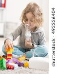 Small photo of Shot of an allergic boy playing with bricks and getting his respiratory theraphy