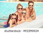 happy family in swimming pool... | Shutterstock . vector #492390424