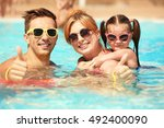 happy family in swimming pool... | Shutterstock . vector #492400090