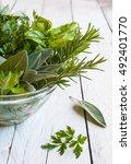 assorted herbs on wooden table | Shutterstock . vector #492401770