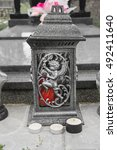 Small photo of Votive candles lantern on the grave in Slovak cemetery. All Saints' Day. Solemnity of All Saints. All Hallows eve. 1st November. Feast of All Saints. Hallowmas. All Souls' Day
