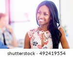 Small photo of Portrait of smiling afro-american office worker sitting in offfice