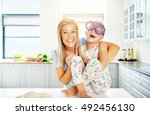 Small photo of Laughing little girl wearing huge purple plastic glasses sitting barefoot on the kitchen counter being hugged by her adoring mother
