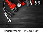 plumber tools on a gray wooden... | Shutterstock . vector #492500239