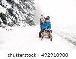 mother pushing son on sledge.... | Shutterstock . vector #492910900