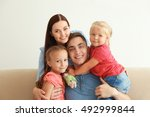 happy parents with daughters at ... | Shutterstock . vector #492999844