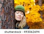 Blonde Girl Hugging Tree Trunk...