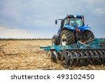 Farmer Riding A Tractor  A...